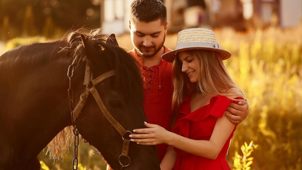 Charming young couple stands with a brown horse before a country house in the rays of evening sun