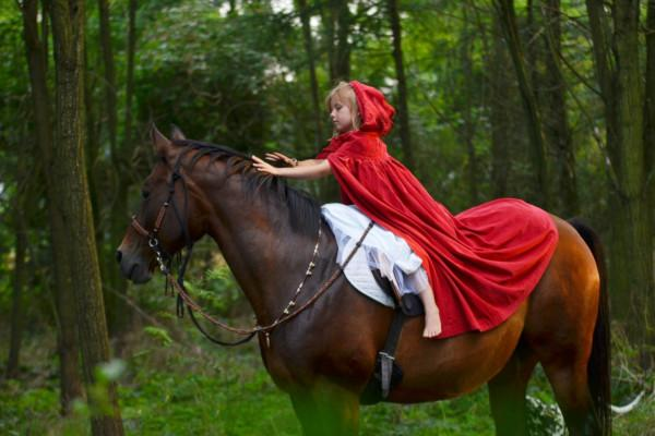 kid in photo session. She is on horseback in the wood