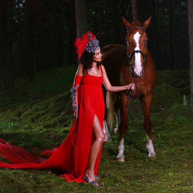 a beautiful woman with brown horse in the wood