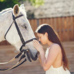 Elegant girl in a long white dress. Lady with horse